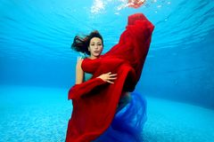 A beautiful teenage girl with a red and blue cloth in her hands posing underwater and looking at the camera. Portrait. Shooting under water. Horizontal Royalty Free Stock Image