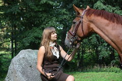 Beautiful teenage girl resting on the rock in park and horse sta Royalty Free Stock Photography
