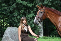 Beautiful teenage girl resting on the rock in park and horse sta Stock Image