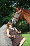 Beautiful teenage girl resting on the rock in park and horse sta Royalty Free Stock Image