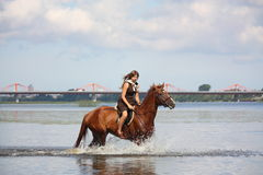 Beautiful teenage girl riding horse in the river Stock Photo