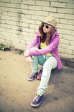 Beautiful teenage girl sits on a skateboard royalty free stock photography