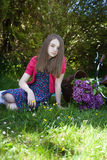 Beautiful teenage girl sitting in a field with a bicycle with a Royalty Free Stock Images