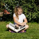 Beautiful teenage girl sitting on a grass in summer park and reads book stock photography