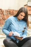 Beautiful teenage girl sitting and reading book on the rustic place.  Stock Photography