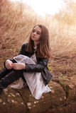 Beautiful teenage girl sitting on a stone wall. Looking into the distance Stock Photography