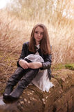 Beautiful teenage girl sitting on a stone wall. Looking into the distance Royalty Free Stock Photos