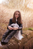 Beautiful teenage girl sitting on a stone wall. Looking looking straight to camera Stock Photo