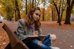 Beautiful teenage girl is sitting and writing in notebook