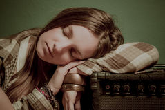 A beautiful teenage girl sleeping on a sound device Royalty Free Stock Photo