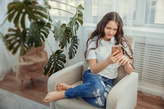 Beautiful teenage girl with smartphone and headphones listening music. Leisure, children, technology and people concept - Beautiful teenage girl with smartphone Royalty Free Stock Image
