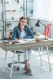 Beautiful teenage girl smiling at camera while sitting at desk and studying. At home stock image