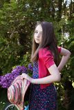 Beautiful teenage girl standing beside a bicycle with a basket o. F flowers looking straight to camera Royalty Free Stock Photography