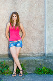 Beautiful teenage girl standing at concrete wall on summer day copy space Stock Photos