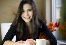 Beautiful teenage girl at table with coffee mug royalty free stock image
