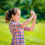 Beautiful teenage girl taking picture with smartphone. In sunny day on summer park. Teenage girl taking selfie with smartphone royalty free stock photo