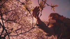 A beautiful teenage girl views magnolia flowers. Spring time stock video footage