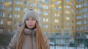 Beautiful teenage girl in warm clothes walking and talking outdoors at winter day stock footage