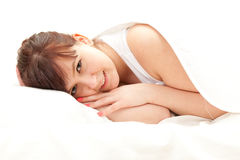 Beautiful teenage girl in white bedding Royalty Free Stock Photography