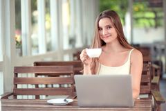 Woman holding drinking a coffee or tea while using laptop stock image