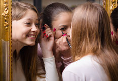 Beautiful girls putting make up in front of the mirror. Beautiful teenage girlfriends having fun while putting make up in front of the old mirror Stock Images
