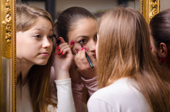 Beautiful teenage girlfriends having fun while putting make up i Royalty Free Stock Image