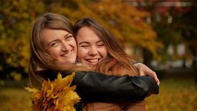 Beautiful Teenage Girls Having Fun in Autumn Park . Two Young Laughing Girls Hugging in the Autumn Park and Holding a. Bouquet of Yellow Leaves. Happy Mood stock video footage