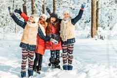 Beautiful teenage girls having fun outside in a wood with snow in winter. Friendship and active life consept stock photography