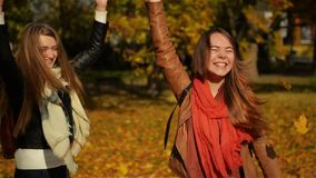 Beautiful Teenage Girls Having Fun While Tossing up Yellow Leaves, Two Young Laughing Girlsfriends Hugging in the Autumn stock footage