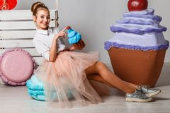 Beautiful teenage girl in pink tutu skirts with lollipops and macaroons and fansy cakes in studio on white background stock photo