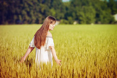 Beautiful Teenage Model girl Dressed in Casual Short Dress on the Field in Sun Light. Royalty Free Stock Photography
