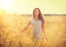 Beautiful teenage model girl outdoors. Beautiful teenage model girl in white dress running on the field Stock Images