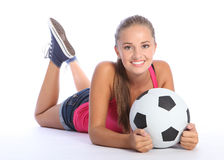 Beautiful teenage soccer girl lying on floor. Fit young teenage athlete girl lying on the floor holding soccer ball with beautiful smile wearing pink vest and Stock Photo