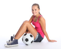 Beautiful teenage student girl with soccer ball. Beautiful soccer player teenage girl with happy smile wearing pink vest and denim shorts, sitting on floor with Royalty Free Stock Images