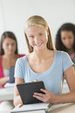 Beautiful Teenage Student Holding Digital Tablet At Desk Royalty Free Stock Image