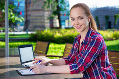 Beautiful teenage student or school girl doing homework in park Stock Images