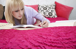 Beautiful Teenage Student Writing In Book On Bed Stock Photo
