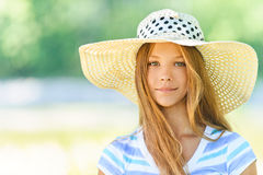 Beautiful teenage in wide-brimmed. Portrait of smiling beautiful teenage in wide-brimmed hat, against green of summer park royalty free stock photo