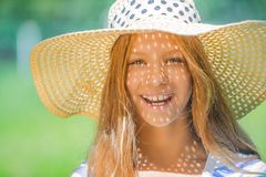 Beautiful teenage in wide-brimmed hat. Portrait of smiling beautiful teenage in wide-brimmed hat, against green of summer park stock image