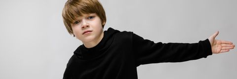 A beautiful teenager in a black sweater and light jeans. The boy spread his hands in both directions. Beautiful teenager in a black sweater. Teenager on a gray stock image