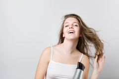 Beautiful teenager blow drying her hair and looking at camera Stock Image