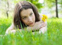Beautiful teenager with dandelion on lawn Royalty Free Stock Image