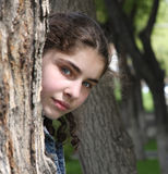 Beautiful teenager girl. Is hiding  behind  the tree Stock Images