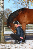 Beautiful teenager girl and bay horse portrait in autumn. With snow on the ground Royalty Free Stock Photography