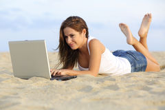 Beautiful teenager girl browsing her laptop lying on the sand of the beach. With the horizon in the background royalty free stock image