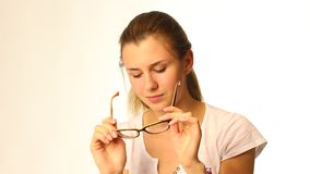 Beautiful teenager girl cleaning her glasses stock video footage