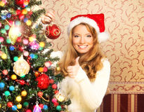 Beautiful teenager girl decorating the Christmas tree Royalty Free Stock Photography