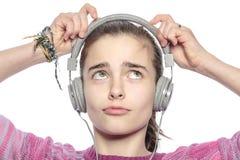 Beautiful teenager girl fumble on her headphones. Isolated on white Stock Image
