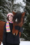 Beautiful teenager girl hugging brown horse in winter Royalty Free Stock Image