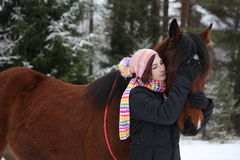 Beautiful teenager girl hugging brown horse in winter Royalty Free Stock Images